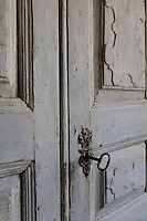 A detail of a rustic wooden door withloc an iron key in a lock