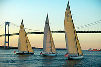 Three twelve meter class sailboats race in the late afternoon light
