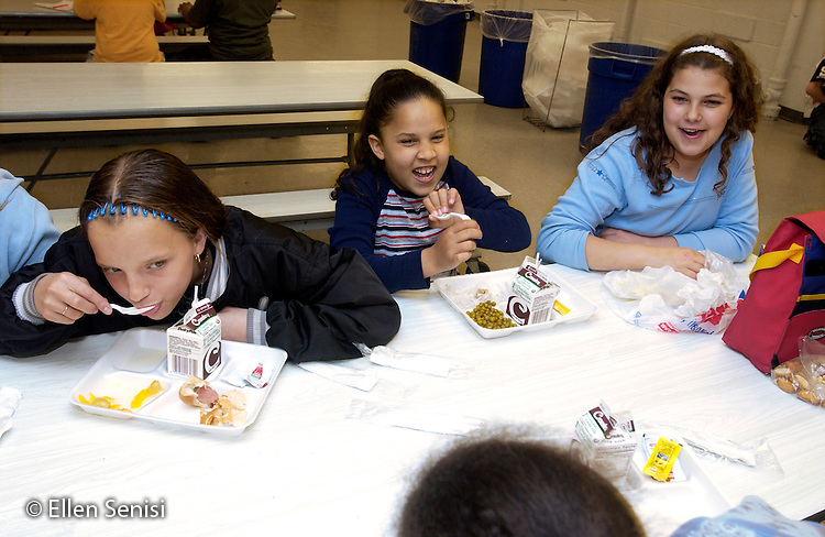 MR / Schenectady, NY / .Yates Arts in Education Magnet School / urban public elementary school / Grade 5.Girl uses fork as sling shot, ready to throw piece of food as students eat and socialize at lunchtime in school cafeteria.  Girls sit with the girls and boys with the boys, exhibiting the self-imposed gender separation often seen at this age. .MR: AD-g2f..© Ellen B. Senisi