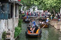 Suzhou, Jiangsu, China.  Boats Take Tourists on Canal Rides in Tongli Ancient Town near Suzhou.  A popular weekend tourist destination.