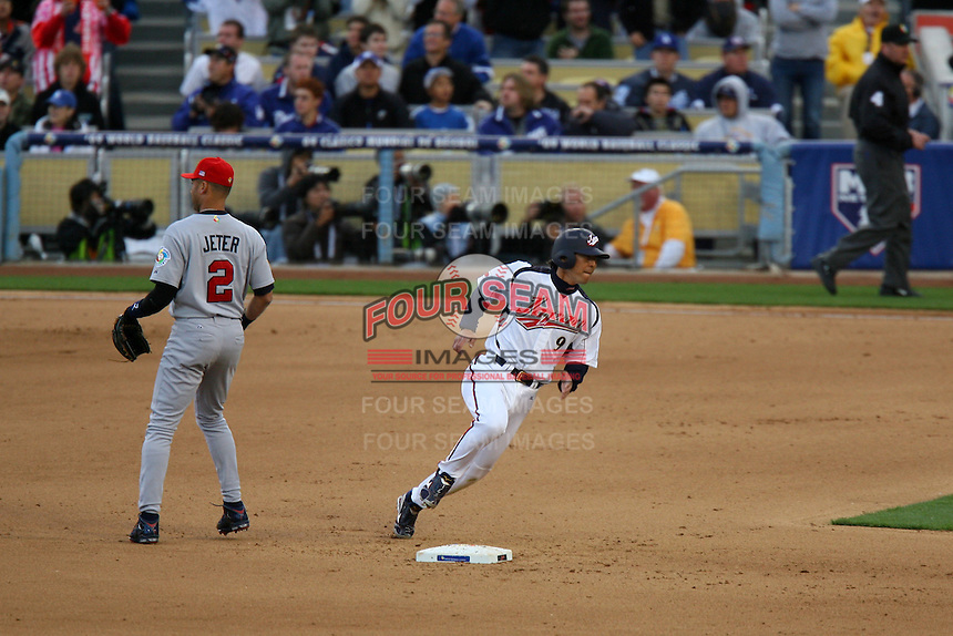 Michihiro Ogasawara of Japan runs past Derek Jeter of the United States during a game at the World Baseball Classic at Dodger Stadium on March 22, 2009 in Los Angeles, California. (Larry Goren/Four Seam Images)