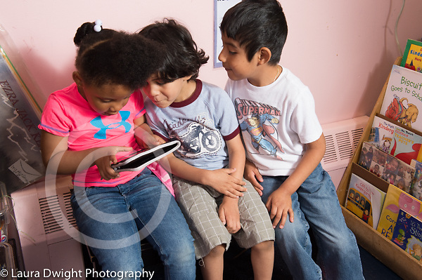 Education preschool 4-5 yearolds group of two boys and a girl absorbed in computer tablet with picture books nearby