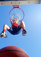 Boy (5-7) hanging from basketball hoop, low angle view