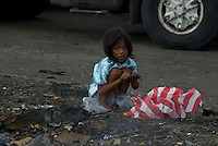 Young Girl Collecting copper wire to sell later view from the car window Manila