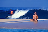 Man on a sandbar with surfer in the background near pipeline, North shore Oahu