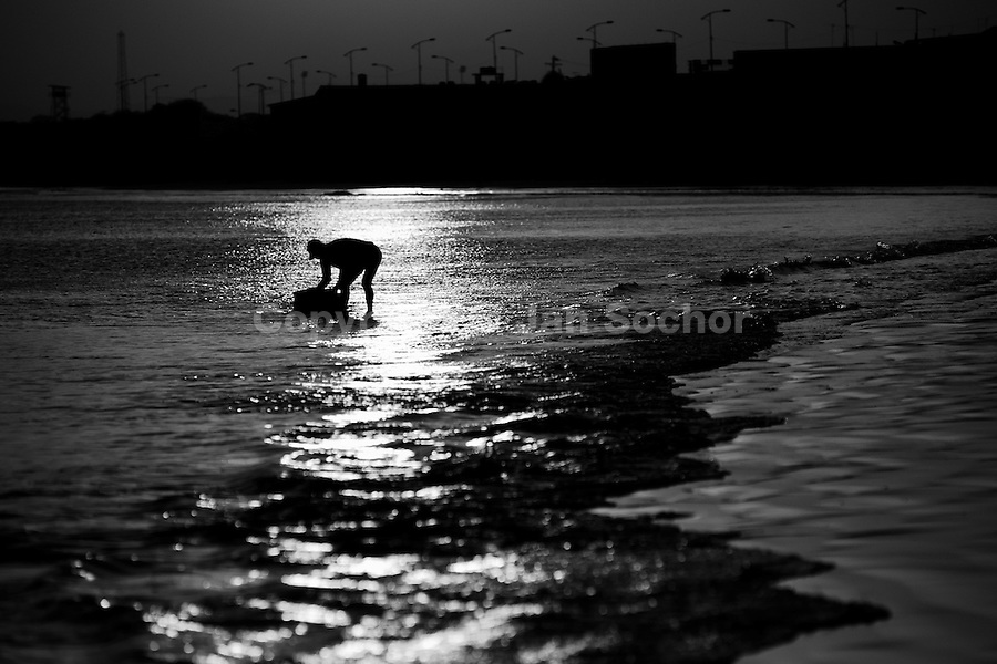 A fisherman cleans up his box in the water at dawn on the beach of Manta, Ecuador, 9 September 2012. Every morning, hundreds of shark bodies and thousands of shark fins are sold on the Pacific coast of Ecuador. Although the targeted shark fishing remains illegal, the presidential decree allows free trade of shark fins from accidental by-catch. However, most of the shark species fished in Ecuadorean waters are considered as ?vulnerable to extinction? by the World Conservation Union (IUCN). Although fishing sharks barely sustain the livelihoods of many poor fishermen on Ecuadorean at the end of the shark fins business chain in Hong Kong they are sold as the most expensive seafood item in the world. The shark fins are primarily exported to China where the shark's fin soup is believed to boost sexual potency and increase vitality. Rapid economic growth across Asia in recent years has dramatically increased demand for the shark fins and has put many shark species populations on the road to extinction.