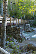 Hiker on footbridge, which cross Franconia Brook along the Lincoln Woods Trail in Lincoln, New Hampshire. Old abutments from Trestle No. 7 of the old the East Branch & Lincoln Logging Railroad (1893-1948) are used to support this bridge. Hikers enter into the Pemigewasset Wilderness on the right-hand side of this bridge.