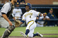 Michigan Wolverines second baseman Ako Thomas (4) slides home against the Oakland Golden Grizzlies on May 17, 2016 at Ray Fisher Stadium in Ann Arbor, Michigan. Oakland defeated Michigan 6-5 in 10 innings. (Andrew Woolley/Four Seam Images)