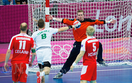 08 AUG 2012 - LONDON, GBR - Goalkeeper Hreidar Levy Gudmundsson (ISL) of Iceland (#16, in dark blue and orange) tries to  save a shot from Gergö Ivancsik (HUN) of Hungary (second from left)  during their men's London 2012 Olympic Games quarter final match at the Basketball Arena in the Olympic Park, in Stratford, London, Great Britain (PHOTO (C) 2012 NIGEL FARROW)