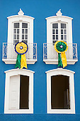 Penedo, Alagoas State, Brazil. Two rossettes in the Brazilian national colours of green, yellow and blue at the windows of a colonial building with four windows painted white in a blue wall.