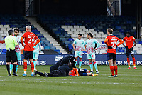 Dan Potts of Luton Town lies motionless on the ground as he is seen by team medical staff during the Sky Bet Championship match between Luton Town and Swansea City at Kenilworth Road, Luton, England, UK. Saturday 13 March 2021