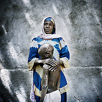 Falta Oumara, 40 with her son Modou, 7, who was badly burned when armed men set fire to their home in Cameroon. One child died in the fire, while two others remain in hospital with severe burns and, two, including Modou live with her in the IDP camp in Meme. Falta fled her village on the night of the attack. <br /> <br /> Falta collects firewood to sell for money in order to buy food. Her children beg for food in the village. Falta has lived in this camp for five months. In her old village her family had a farm. 'I ate what I wanted. Now, life is very difficult.'