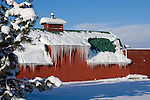 Icicles hang off the eaves of a red barn.