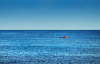 Man in small wooden rowboat on the vast blue ocean, Negril, Jamaica