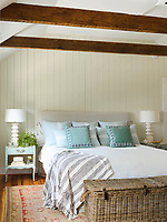 A country style bedroom with cream wood panelling and a beamed ceiling. The double bed has a grey upholstered headboard and bedside lamps on blue bedside cabinets. A wicker basket stands at the end of the bed.