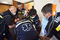 Switzerland. Canton Ticino. Mezzovico. A senior man is carried seated on a chair, then by ambulance to the hospital for medical examinations. The elderly man is suffering from severe respiratory problems. The emergency doctor Daniele Speciale (with beard and glasses) is working with four paramedics. They all work for theCroce Verde Lugano. They wear blue uniforms, medical gloves and surgical masks. The man (C) and the woman (C) are professional certified nurses, both men (L) (R) are volunteers specifically trained in emergency rescue. The senior citizen has a mask on his face and receives oxygen from a medical ventilator carried by the doctor. A medical ventilator (or simply ventilator in context) is a mechanical ventilator, a machine designed to move breathable air into and out of the lungs, to provide breathing for a patient who is physically unable to breathe, or breathing insufficiently. TheCroce Verde Lugano is a private organization which ensure health safety by addressing different emergencies services and rescue services. Volunteering is generally considered an altruistic activity where an individual provides services for no financial or social gain to benefit another person, group or organization. Volunteering is also renowned for skill development and is often intended to promote goodness or to improve human quality of life. Medical gloves are made of different polymers including latex, nitrile rubber, polyvinyl chloride and neoprene. 14.01.2018 © 2018 Didier Ruef