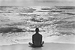 SOUTH BEACH MIAMI FLORIDA - USA JUNE 1999.A LONE MAN SITS ON THE BEACH IN THE LOTUS POSITION FACING THE OCEAN.