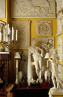The yellow walls of the drawing room are covered with a   collection of architectural plaster reliefs