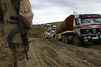 A policemen guards the road as trucks try to overcome the mud infested track that they must pass in order to reach Tarin Kot