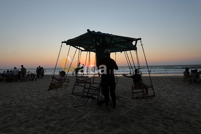 Palestinians enjoy their time at the beach of Deir al-Balah sea, in the center of Gaza Strip, during a hot day on August 10, 2021. The beach is one of the few open public spaces in this densely populated city. Photo by Ashraf Amra