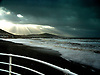 Heavy storm clouds over Aberystwyth Beach as the last rays of sunlight sneak through.<br /> <br /> Stock Photo by Paddy Bergin