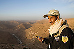 Arabian Leopard (Panthera pardus nimr) researcher Waleed Al'Rail checking gps to find camera trap in sandstone desert, Hawf Protected Area, Yemen