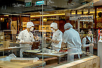 Chefs working in a pastry shop in the shopping mall at the Marina Bay Sands resort hotel.