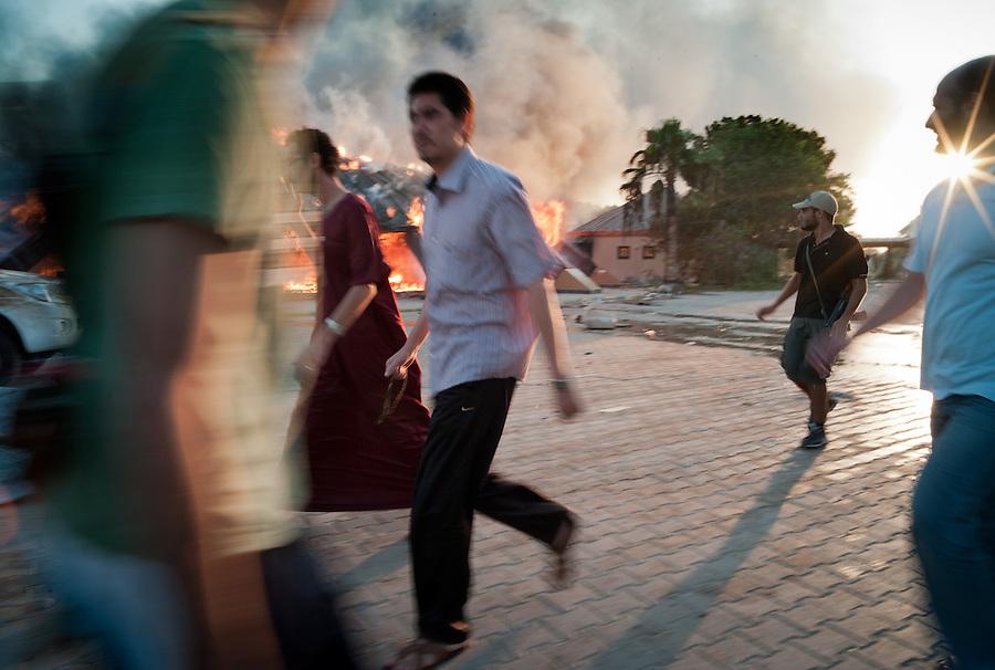 Libyan men pass burning Gaddafi tent in the Bab Al Aziziya compound in Tripoli, Libya