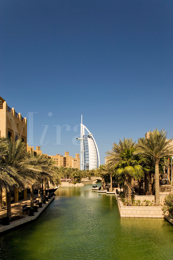 Dubai.  View over Madinat Jumeirah and Mina a?Salam Hotel of Burj al Arab Hotel, architect W.S. Atkins, an icon of Dubai built in the shape of the sail of a dhow, stands on an island off Jumeirah Beach.  .