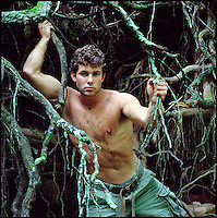 Bare chested man leaning through tree roots<br />