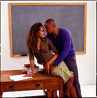 African American couple embracing on edge of desk<br />