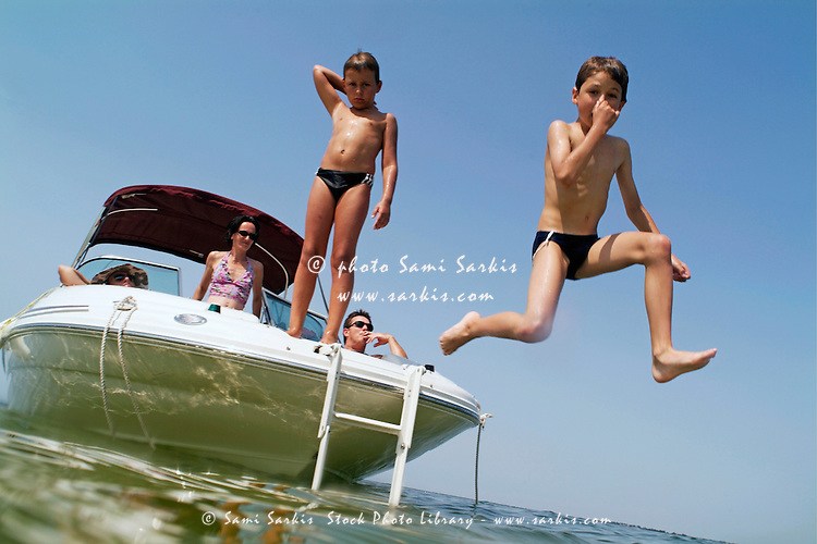 Two young boys jumping from a boat into the sea near Biscarrosse, Bordeaux, France.
