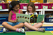 MR / Schenectady, NY. Zoller Elementary School (urban public school). Kindergarten classroom. Two bilingual students read Spanish-language book in class. Book is entitled Amigos de todas clases, ¡hasta verdes!  (All Kinds of Friends, Even Green) by Ellen Senisi. Left: girl, 6, Hispanic-American; Right: girl, 5; both are native Spanish speakers. MR: Fue3, Cas12. ID: AM-gKw. © Ellen B. Senisi.