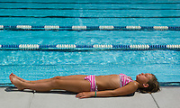 Young girl, 12-15, in two-piece bathing suit, lies at edge of pool to sunbath.