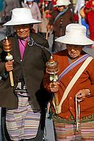 Tibetan Buddhist women wearing traditional aprons, with prayer wheels and rosary beads, walking the Barkhor pilgrim circuit around the Jokhang Temple during the Saga Dawa festival, Lhasa, Tibet.