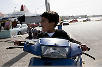 Pictured: A young boy seems to be getting amused with a parked moped Monday 07 March 2016<br /> Re: Migrants have been gathering at the port of Piraeus, near Athens, Greece.
