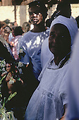 Salvador, Brazil. Festa de Yemanja; Candomble woman in traditional while lace dress and headscarf; effigy of the goddess.