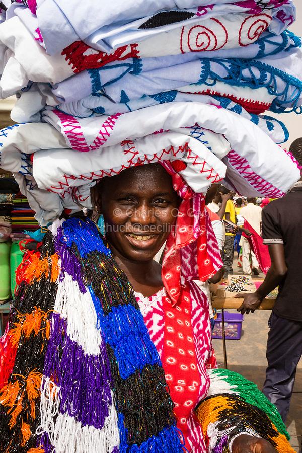 Senegal, Touba.  Woman Selling Cloth in the Market.