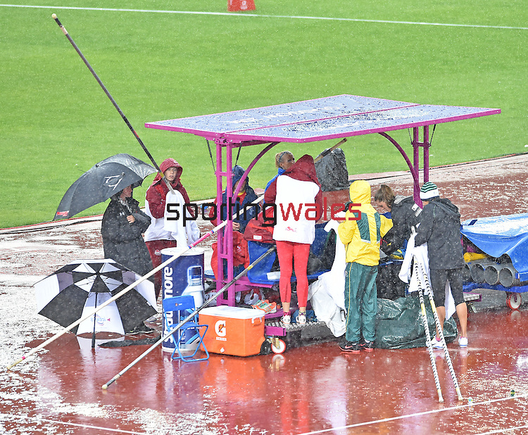 Wales' Sally Peake, left, shelters under an umbrella during a down pour of rain as she waits for the women's pole vault competition to start<br /> <br /> Photographer Chris Vaughan/CameraSport<br /> <br /> 20th Commonwealth Games - Day 10 - Saturday 2nd August 2014 - Athletics - Hampden Park - Glasgow - UK