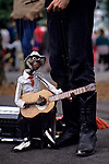 Street performer with puppet playing the guitar and singing