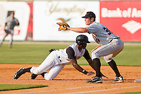 Kenny Gilbert #26 of the Kannapolis Intimidators dives back to first base as Mike Flacco #39 of the Delmarva Shorebirds waits for the throw at Fieldcrest Cannon Stadium on May 22, 2011 in Kannapolis, North Carolina.   Photo by Brian Westerholt / Four Seam Images