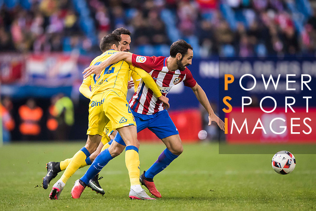 """Juan Francisco Torres Belen """"Juanfran"""" (r) of Atletico de Madrid competes for the ball with Helder Lopes and Jeronimo Figueroa Cabrera """"Momo"""" of UD Las Palmas during their Copa del Rey 2016-17 Round of 16 match between Atletico de Madrid and UD Las Palmas at the Vicente Calderón Stadium on 10 January 2017 in Madrid, Spain. Photo by Diego Gonzalez Souto / Power Sport Images"""