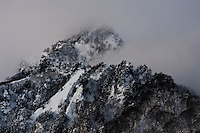 The rugged peak of Togakushi Mountain disappointing behind cloud on a snowy winter afternoon in northern Nagano Prefecture, Japan.