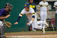 Michigan Wolverines second baseman Ramsey Romano (4) slides safely home during the NCAA baseball game against the Washington Huskies on February 16, 2014 at Bobcat Ballpark in San Marcos, Texas. The game went eight innings, before travel curfew ended the contest in a 7-7 tie. (Andrew Woolley/Four Seam Images)