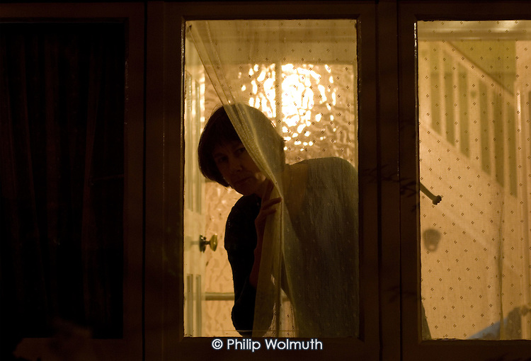 A woman looks out of a window at night