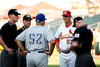 Manager Ron Warner (57) of the Springfield Cardinals meets with Duane Espy (52) of the Tulsa Drillers and umpires prior to a game against the Tulsa Drillers at Hammons Field on July 20, 2011 in Springfield, Missouri. Springfield defeated Tulsa 12-1. (David Welker / Four Seam Images).