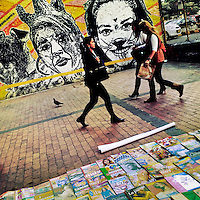 Colombian women walk in front of a graffiti stencil artwork, created by an artist named Dj Lu, in the center of Bogotá, Colombia, 16 February, 2016. A social environment full of violence and inequality (making the street art an authentic form of expression), with a surprisingly liberal approach to the street art from Bogotá authorities, have given a rise to one of the most exciting and unique urban art scenes in the world. While it's technically not illegal to scrawl on Bogotá's walls, artists may take their time and paint in broad daylight, covering the walls of Bogotá not only in territory tags and primitive scrawls but in large, elaborate artworks with strong artistic style and concept. Bogotá has become an open-air gallery of contemporary street art.