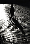 Silhouetted man standing on cobblestone street