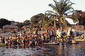 Kalepo, Tanzania. Village children knee-deep at the water's edge waving; Lake Tanganyika.