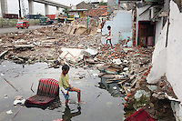 Children walk through ruins of a flooded district in the northern port area of Jakarta. Almost 40% of Jakarta lies below sea-level leading to flooding in many areas, even during the dry season.